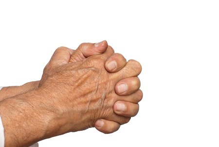 praying together: Clasped hands in prayer - isolated on white