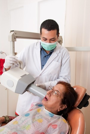 A dentist takes the x-ray of a patient