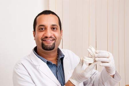 An Indian  Asian dentist with teeth mold