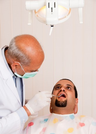 A senior Indian  Asian dentist takes a look at a patient Stock Photo