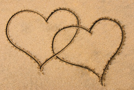 entangled: Two entangled hearts drawn out on a sandy beach