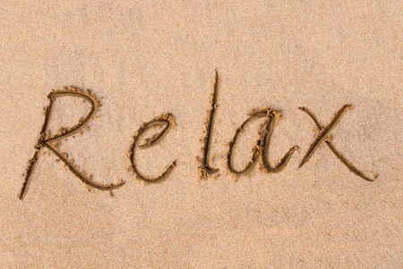 relaxation background: The word Relax written out on a sandy beach