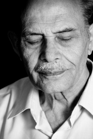 A portrait of a senior Asian man with his eyes closed. Monochrome. photo