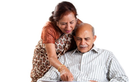 A senior Indian  Asian couple pointing at a newspaper - isolated on white