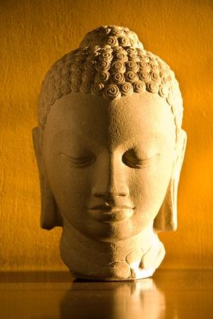 stone buddha: A statue of Buddha against a yellow background