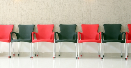 A line of alternating Black and red plastic chairs photo