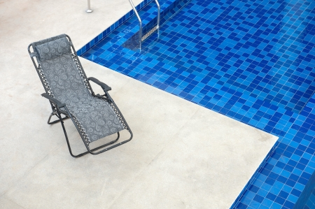 pool deck: Reclining chair along a swimming pool Stock Photo