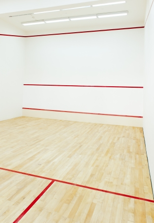 An empty squash court with a wooden floor