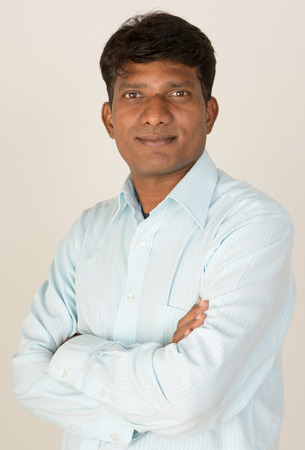 An Indian  South Asian business executive with folded arms looking to camera. On grey background. photo
