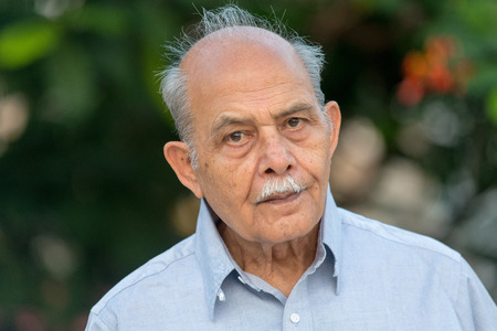 An outdoor photo of a senior Indian  South Asian man looking to camera
