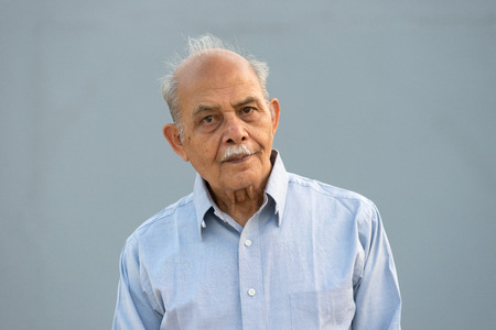 elderly adults: A senior Indian  South Asian man against a light blue background