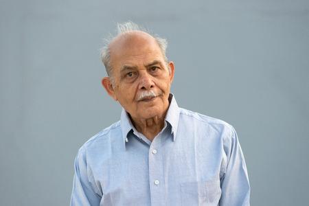 Ein hochrangiger indischer / South Asian Mann gegen einen hellblauen Hintergrund