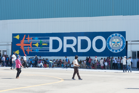 Bengaluru, India - February 22, 2019: Visitors at the Aero India 2019 rest from the shade outside the DRDO hall. Aero India is a biennial air show and aviation exhibition.