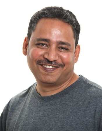 A smiling Indian man in a studio against a white background Zdjęcie Seryjne