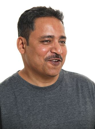 A smiling Indian man in a studio against a white background - looking away