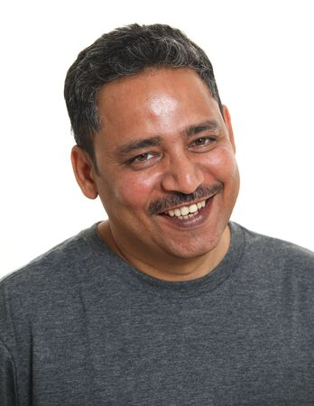 A smiling Indian man in a studio against a white background Imagens