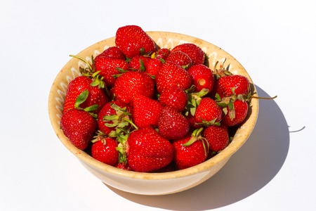 Ripe red strawberries  lying in plate isolated on white background. The juicy fruit for diet food. photo