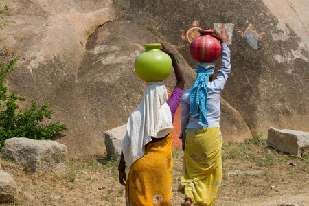 back of head: Two Indian women carry water on their heads in traditional pots