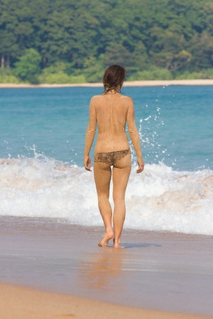 naked youth: Young women enters the sea. Indian ocean.