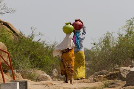 Twee Indische vrouwen dragen water op hun hoofd in traditionele potten