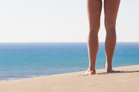 footprints in the sand: Womens legs from behind. Recreation. Footprints. Sand texture