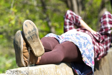 girl soles: Macro photo of shoe soles. Girl resting on nature after a long physical activity