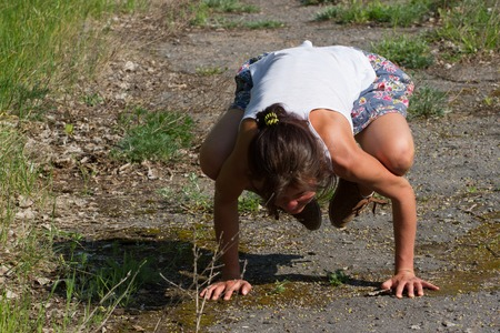 commits: Yoga postures. Fit girl commits bakasana outdoors