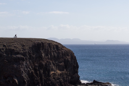 Scenic large rock overlooking the sea. Bicyclist on a background of sky and stone, Papagayo beach Lanzarote Stock Photo