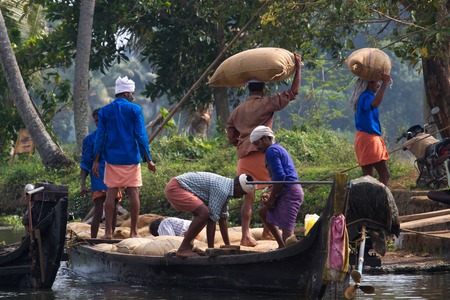 allepey: ALLEPPEY, KERALA, INDIA, MARCH 31, 2015: Some men transport, overload, put on them head dwell of rice