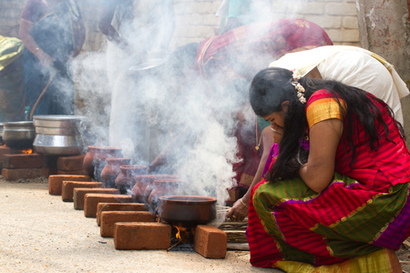 act of god: KOVALAM, KERALA, INDIA, April 1, 2015: Some women devotees participate in Pongala ceremony where boiled rice made in clay pots is offered to the god