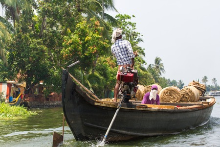 allepey: Allepey, Kerala, India March 31, 2015: Indian man transport dwell with rice for boats. backwaters canoe in state,.