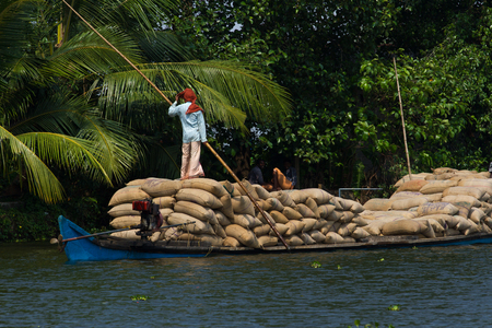 allepey: Allepey, Kerala, India March 31, 2015: Indian man transport dwell with rice for boats. backwaters canoe in state,. Cochin Editorial