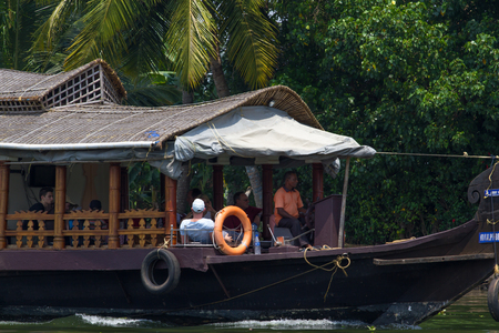 backwaters: Allepey, Kerala, India, March 31, 2015: Unidentified indian man and tourists are sailing in houseboat on backwaters Allapuzha city Editorial