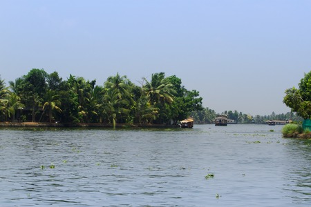 alappuzha: Allepey, Kerala, India, March 31, 2015: Unidentified indian man and tourists are sailing in houseboat on backwaters Allapuzha city Editorial