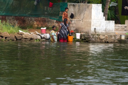alappuzha: Allepey, Kerala, India, March 31, 2015: Unidentified indian woman wash clothes in front of his house on the water Editorial