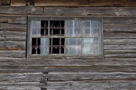 spall: Part of the wooden wall of old antique house with broken windows and pine frame