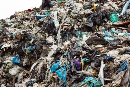 Pile of plastic bags and other refined petroleum products dumped in landfill. Garbage heap gives infiltrate into groundwater. Waste sorting is required. Lviv city Stock Photo