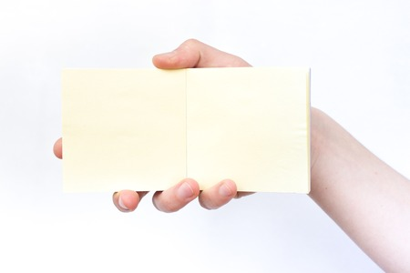 yellow notepad: Hand holds notebook open. Blank white paper. Place for inscription, Clean place for new idea Stock Photo