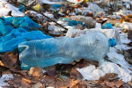 Stapel van plastic zakken en andere geraffineerde aardolieproducten die op stortplaats worden gedumpt. Vuilnisbelt geeft infiltratie in het grondwater. Afval sorteren is verplicht. Blauwe plastic fles,