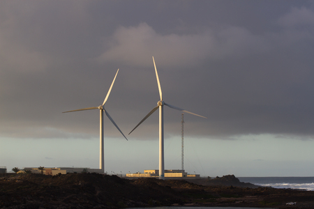 alternative energy sources: Two wind farms against background of setting sun. Alternative power supplies. Canary islands Stock Photo