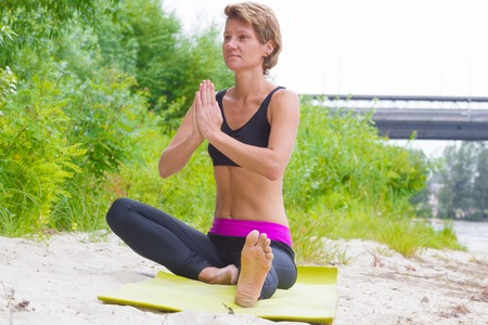 kundalini: Hatha yoga. Seated half lotus, Yoga poses, asan. Concept of healthy life and natural. Practicing yoga, sitting and fold ones hands in namaste, wearing sportswear, bra, park, outdoor