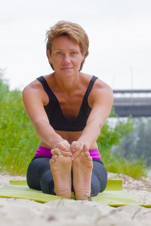 kundalini: Hatha yoga. Paschimottanasan. Yoga poses, asan. Titl to feet. Concept of healthy life. Practicing yoga, Janu Sirsasana pose, wearing sportswear, bra