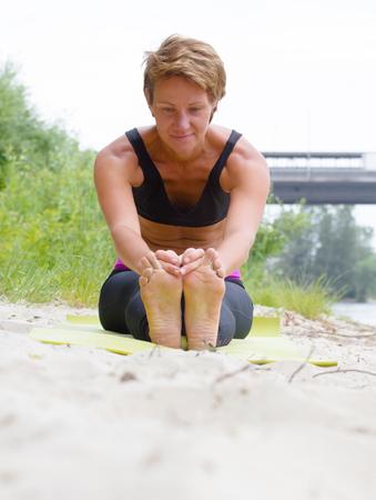 janu: Hatha yoga. Paschimottanasan. Yoga poses, asan. Titl to feet. Concept of healthy life. Practicing yoga, Janu Sirsasana pose, wearing sportswear, bra