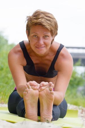 ashtanga: Hatha yoga. Paschimottanasan. Yoga poses, asan. Titl to feet. Concept of healthy life. Practicing yoga, Janu Sirsasana pose, wearing sportswear, bra