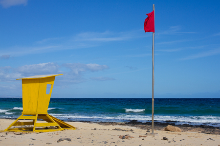 Yellow lifeguard tower. One life guard together red flag on beach. Point of safe, surviving. Coastal view.