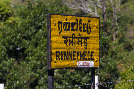 Nilgiri. Railroad sign Runneymede written in Tamil official language of Tamilnadu , Hindi and English on a platform of railway station