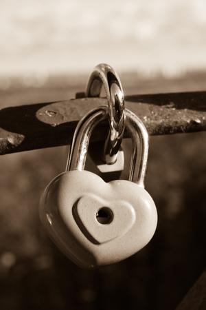 Symbool van liefde. Uitstekende kaart met rode hartachtergrond. Metalen slot op de brug van geliefden. Retro stijl. Sepia kleurtonen.