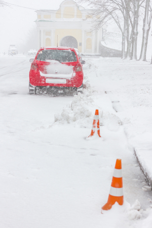 Snowstorm and snow-covered street and cars with a lonely pedestrian. Orange barrier Stock Photo