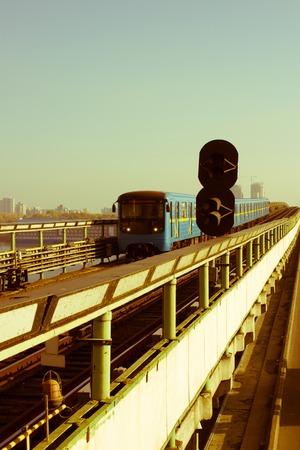Subway train on metro-bridge, approaching Dnipro station, Kiev, Ukraine. Retro style Stock Photo