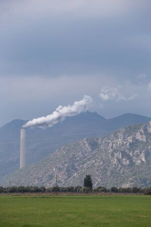 Environmental Pollution. White steam comes from the pipe. Industry factory on the field. Landscape green background.